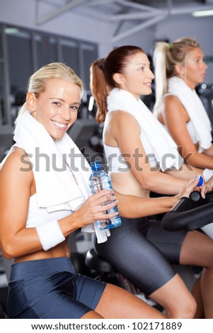 young woman drinking water while cycling in gym - stock photo