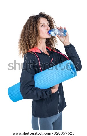 Young woman drinking water while holding exercise mat against white background