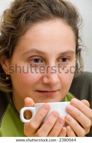 young woman drinks coffee from white cup