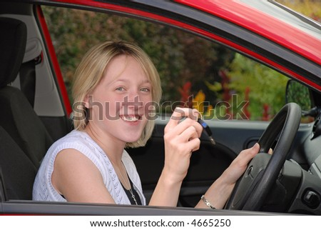 Young woman driver holding key in car