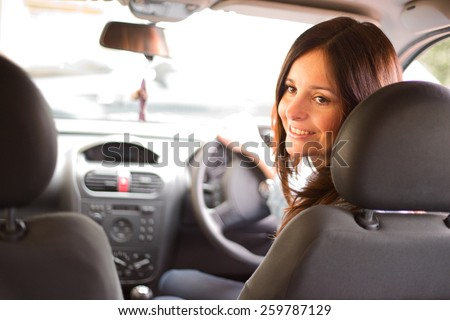 young woman driver talking to a passenger. - stock photo