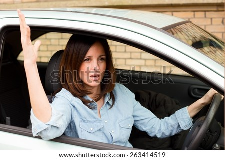 young woman driver waving hand annoyed.  - stock photo