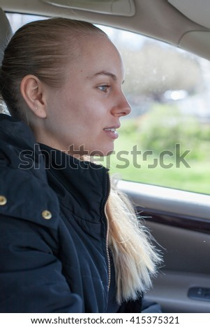 Young woman driving a car, being focused on the traffic.