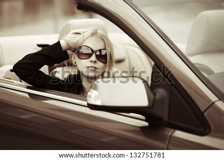 Young woman driving a convertible car - stock photo