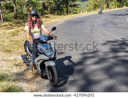 Young woman driving a scooter at the beach - stock photo