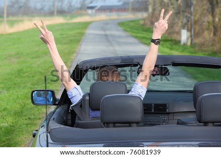 Young woman driving a sports cabriolet car - stock photo