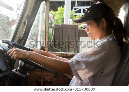 young woman driving a truck - stock photo