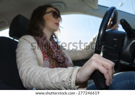 Young woman driving car. Beautiful and stylish lady sitting in car holding steering wheel grip white jacket lips face make up blue sky window vehicle interior Focus on hand changing transmission grip  - stock photo
