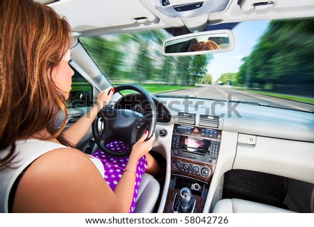 Young woman driving car. Fast motion effect. - stock photo