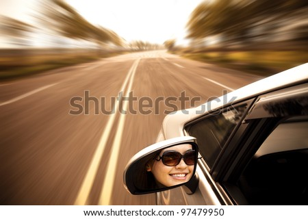 young woman driving car on the road - stock photo