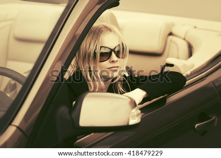 Young woman driving convertible car. Female fashion model in sunglasses outdoor - stock photo