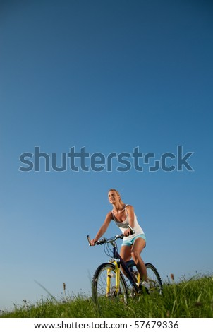 young woman driving on a mountain bike in her free time - stock photo