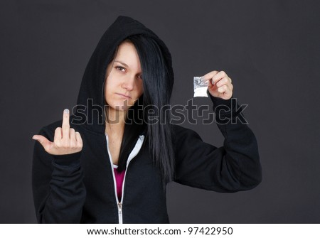 Young woman drug addict or dealer showing a packet of drugs and giving the viewer the finger. - stock photo