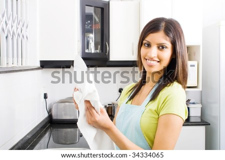 young woman drying dishes in kitchen - stock photo