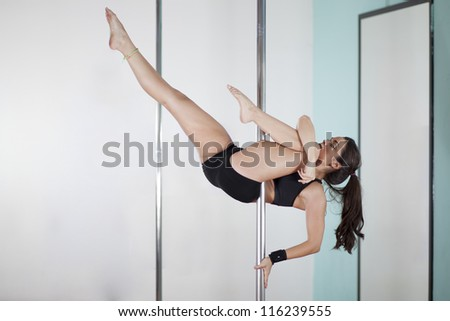 Young woman during a pole fitness class