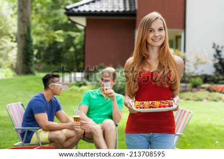 Young woman during garden party with friends - stock photo
