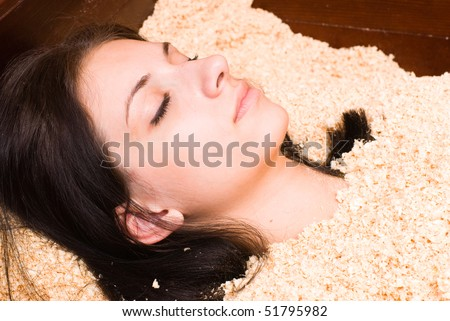 Young woman during ofura bath procedure with cedar sawdust in japanese spa