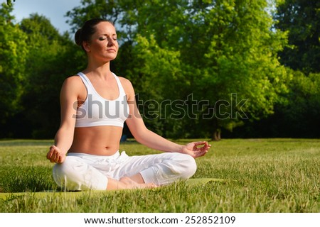 Young woman during yoga meditation in the park. - stock photo