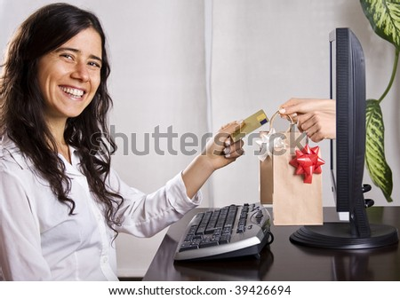 Young woman e-shopping from home. Hands and bags coming out from the computer screen. - stock photo
