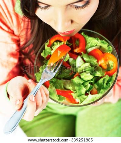 Young woman eat vegetarian food. Green salad.. - stock photo