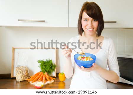 Young woman eating a bowl of muesli in her kitchen - stock photo