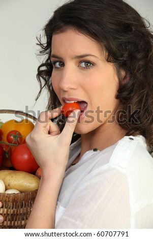 Young woman eating a cherry tomato