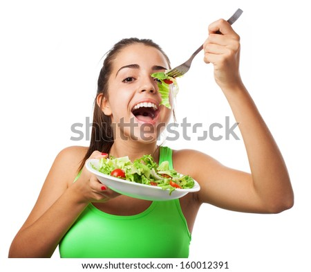 young woman eating a fresh salad isolated on white background