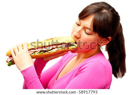 young woman eating a freshly made sub sandwich isolated on white - stock photo