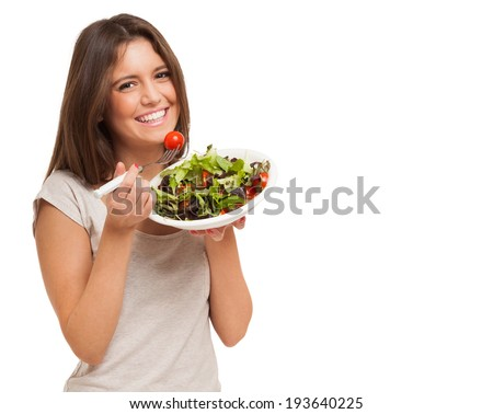 Young woman eating a healthy salad - stock photo