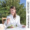 Young woman eating a healthy salad outdoors on restaurant patio - stock photo