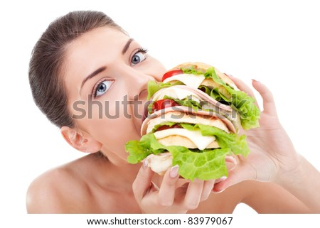 Young woman eating a huge sandwich on white background stock photo