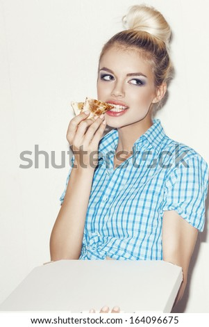 Young woman eating a piece of pizza. Indoors, lifestyle. - stock photo