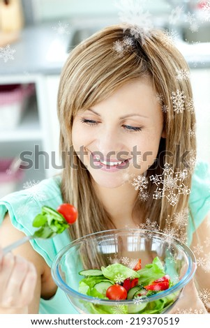 Young woman eating a salad in the kitchen with snow falling - stock photo