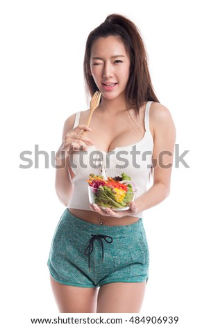 Young woman eating a vegetable salad on white background