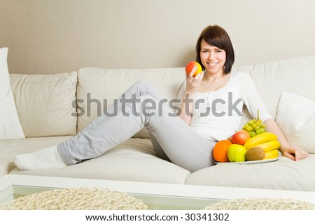 Young woman eating an apple on a couch - stock photo