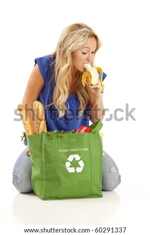 Young woman eating banana from green grocery bag - stock photo