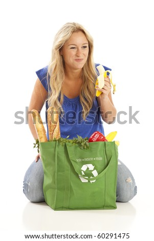 Young woman eating banana from green grocery bag