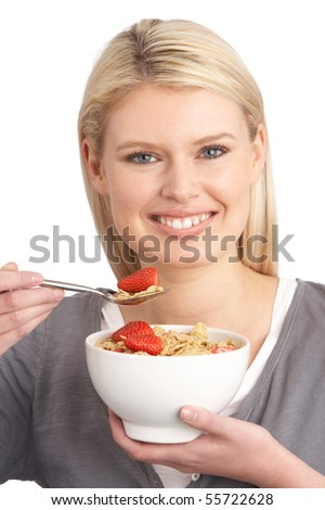 Young Woman Eating Bowl Of Healthy Breakfast Cereal In Studio - stock photo