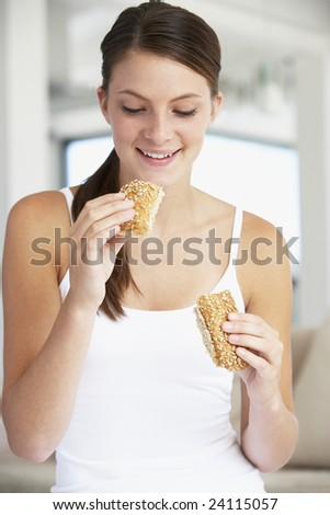 Young Woman Eating Brown Bread Roll
