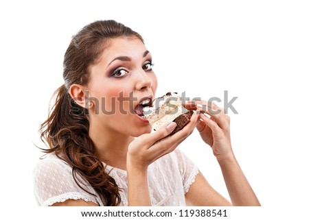 Young woman eating cake, isolated over white background - stock photo