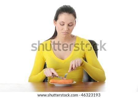 Young woman eating carrot from plate, isolated on white - stock photo
