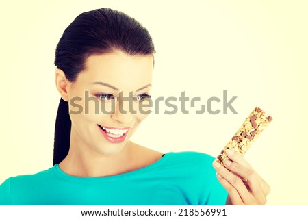 Young woman eating Cereal candy bar, isolated on white - stock photo