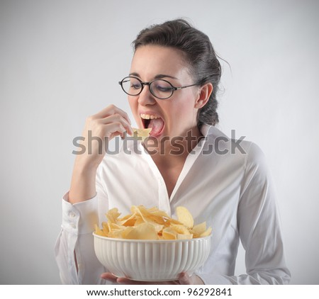 Young woman eating chips - stock photo