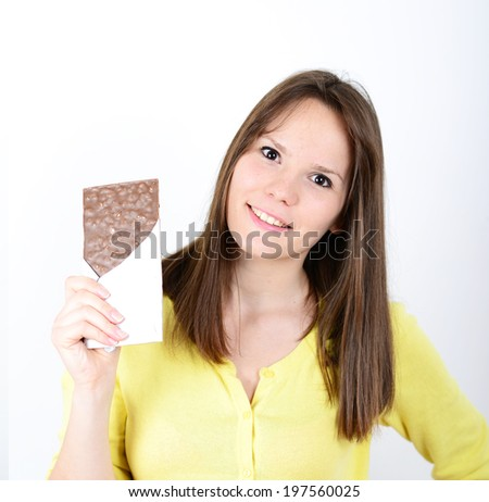 Young woman eating chocolate bar against white background