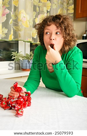 Young woman eating chocolate sweets - stock photo