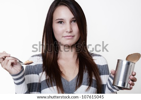 young woman eating cold bake beans from the tin - stock photo