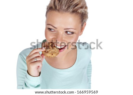 Young woman eating cookie - stock photo