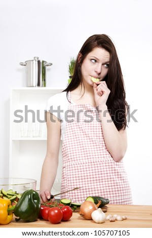young woman eating cucumber while preparing salad - stock photo