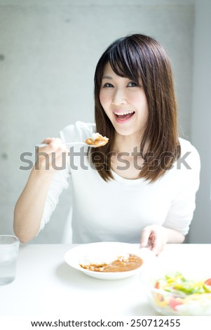 young woman eating curry - stock photo
