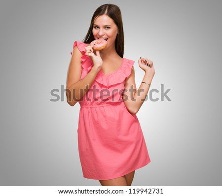 Young Woman Eating Doughnut against a grey background - stock photo